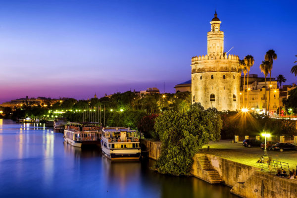 Golden tower on riverbank at night, Seville