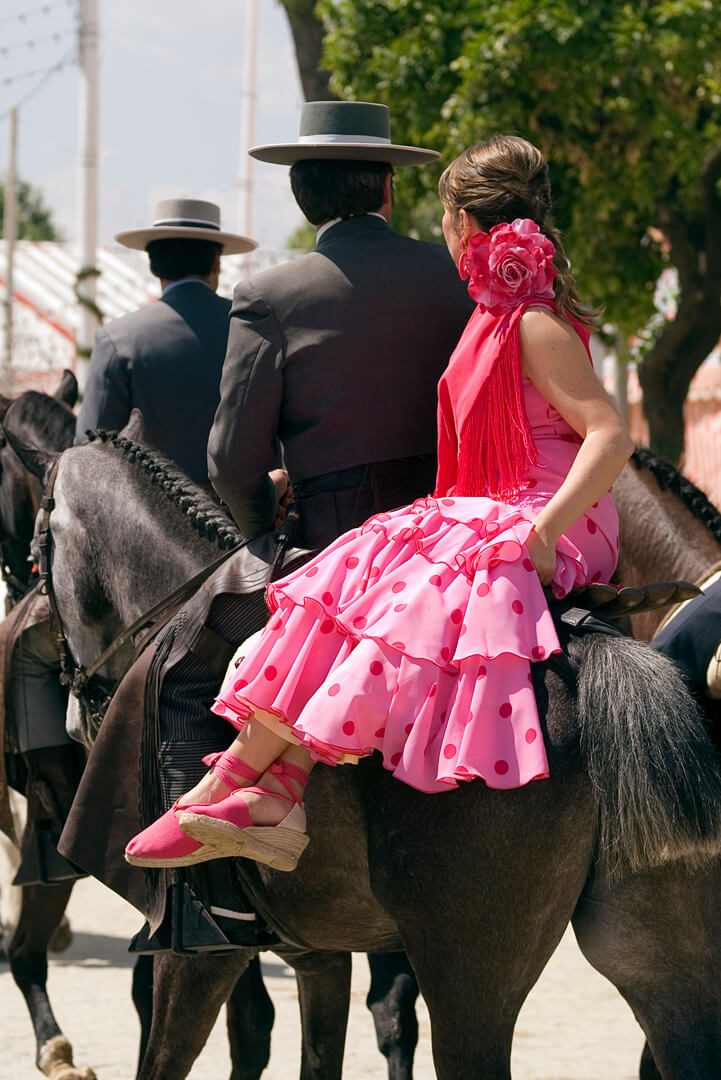 Girl in flamenco dress on horseback in Seville Fair, Spain